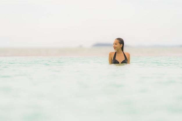 Bello giovane bikini asiatico di usura di donna del ritratto intorno alla piscina nella spiaggia dell'oceano del mare quasi della località di soggiorno dell'hotel Foto Gratuite