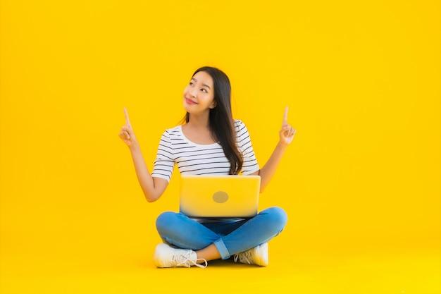 Bello giovane computer portatile asiatico di uso della donna del ritratto Foto Gratuite