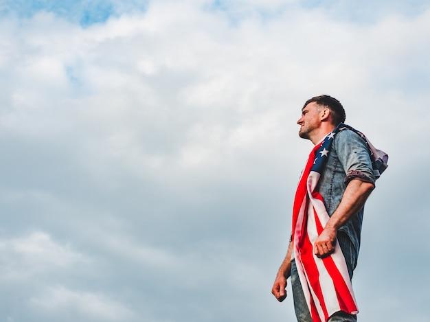 Bello, giovane in possesso di una bandiera americana Foto Premium