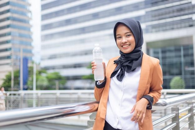 Bello giovane musulmano asiatico con acqua in bottiglia. Foto Premium