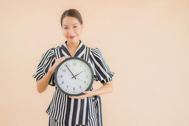 Bello giovane orologio o allarme asiatico di manifestazione della donna del ritratto Foto Gratuite