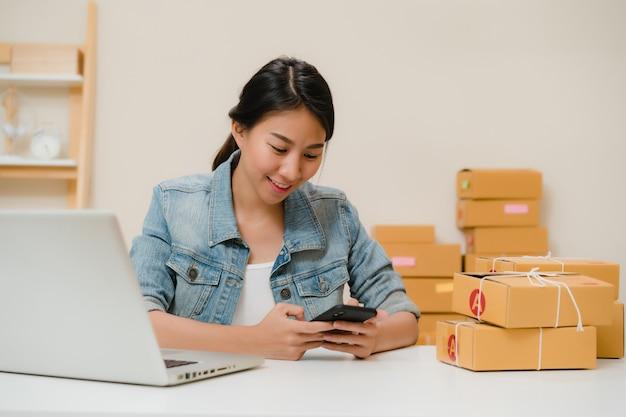 Bello giovane proprietario di donna asiatico astuto di affari dell'imprenditore della pmi che controlla prodotto sul codice di qr di ricerca di riserva che lavora a casa. Foto Gratuite