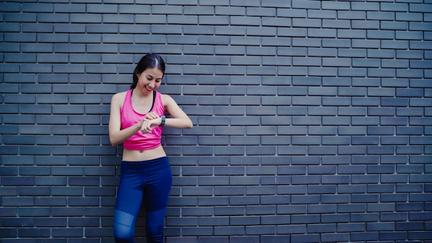 Bello giovane regolazione asiatica in buona salute della donna dell'atleta e controllo di progresso che guarda il monitor di frequenza cardiaca Foto Gratuite