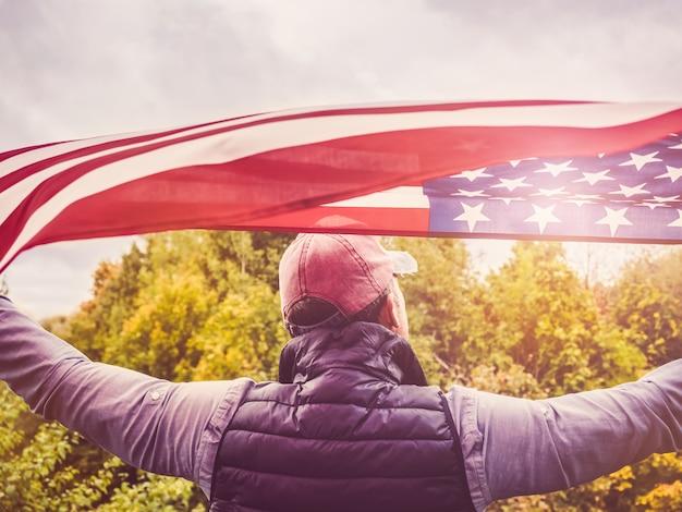 Bello, giovane uomo sventolando una bandiera americana Foto Premium