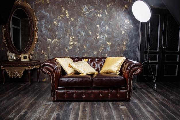 Bello interno lussuoso d'annata del sofà di marrone scuro con la parete concreta grigia di struttura nella sala. Foto Premium