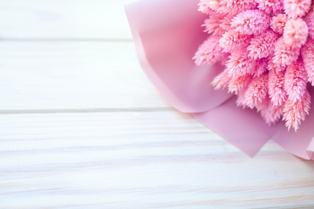 Bello mazzo dei fiori rosa asciutti su un fondo bianco di legno Foto Premium