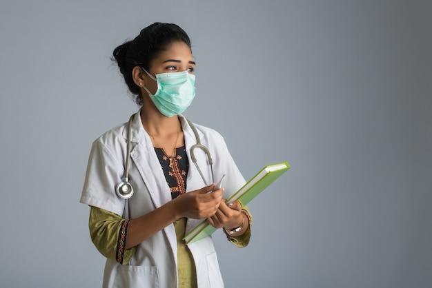 Bello medico della giovane donna con il termometro e rapporto o libro Foto Premium
