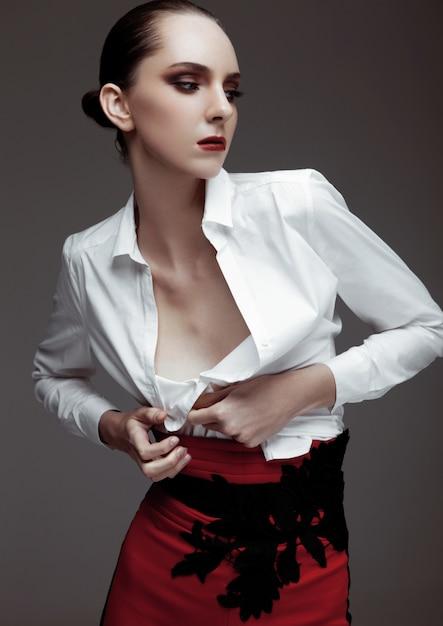 Bello modello di moda che porta i pantaloni rossi e la camicia bianca su fondo grigio Foto Premium