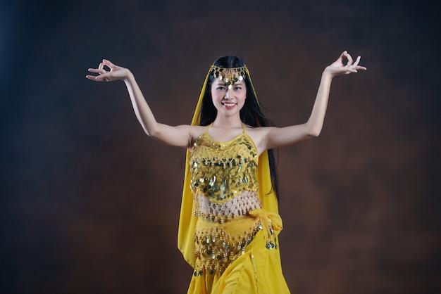 Bello modello indiano giovane della donna indù. saree giallo tradizionale del costume indiano. Foto Gratuite