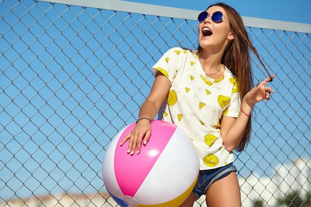 Bello modello sorridente alla moda della giovane donna di fascino pazzo divertente in abbigliamento casual di estate luminosa dei pantaloni a vita bassa che posa nella via dietro la griglia e il cielo blu del ferro. giocando con il floa colorato gonfiabile Foto Gratuite