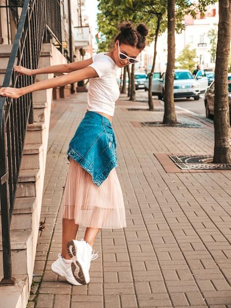 Bello modello sorridente con l'acconciatura di corna vestita in abiti jeans giacca estiva pantaloni a vita bassa ragazza spensierata sexy in posa in strada. donna divertente e positiva di tendenza divertendosi in occhiali da sole Foto Gratuite