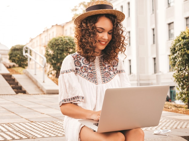Bello modello sorridente con l'acconciatura di riccioli afro vestito in abito bianco hipster estate. Foto Gratuite