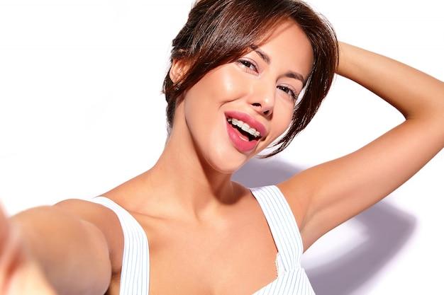 Bello modello sveglio sorridente della donna del brunette in vestito casuale da estate senza trucco con le parentesi graffe bianche sui denti che fanno la foto del selfie sul telefono, isolato Foto Gratuite
