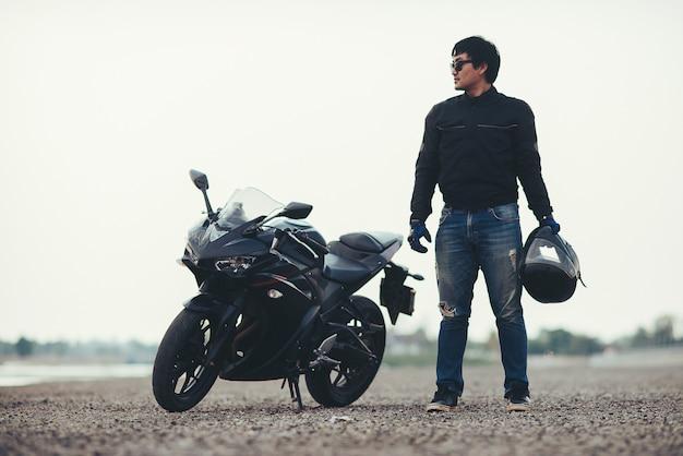 Bello motociclista con il casco nelle mani della moto Foto Gratuite