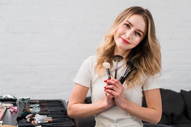 Bello mucchio della tenuta della donna di spazzole cosmetiche Foto Gratuite