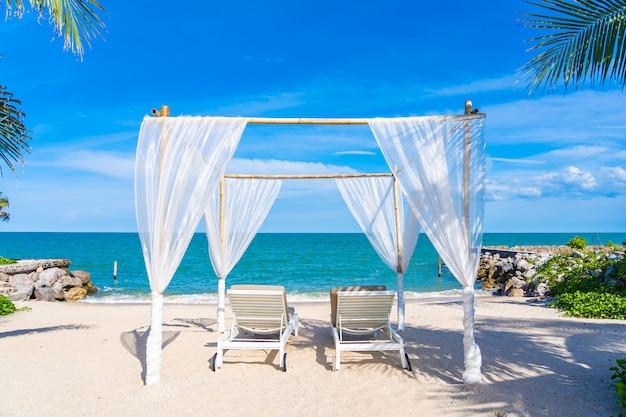 Bello ombrello e sedia intorno all'oceano del mare della spiaggia con cielo blu per il viaggio Foto Gratuite