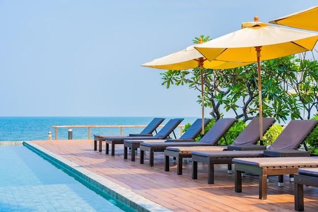 Bello ombrello vuoto della sedia intorno alla piscina all'aperto nella località di soggiorno dell'hotel per il viaggio Foto Gratuite