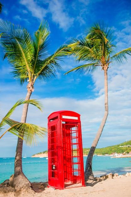 Bello paesaggio con una cabina telefonica classica sulla spiaggia sabbiosa bianca in antigua Foto Premium
