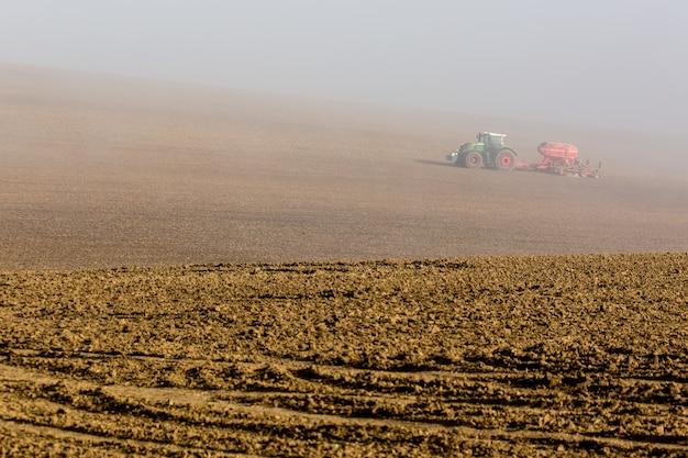 Bello paesaggio nebbioso nebbioso di autunno con il trattore funzionante nella moravia del sud, repubblica ceca. Foto Premium