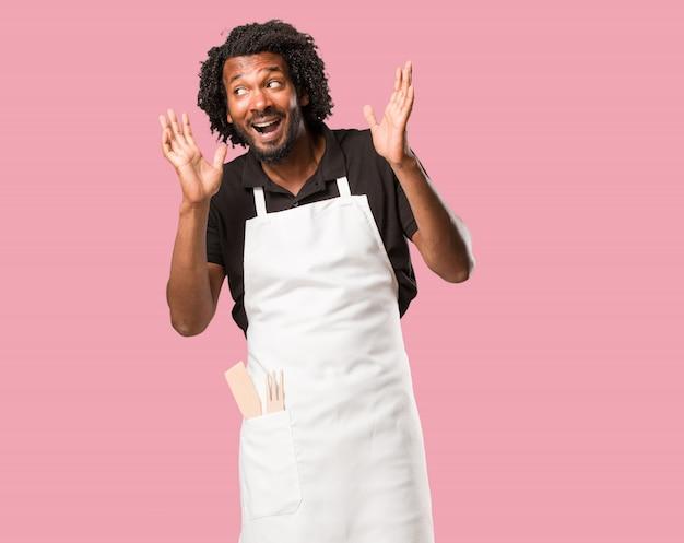 Bello panettiere afroamericano sorpreso e scioccato, guardando con gli occhi spalancati, eccitato da un'offerta o da un nuovo lavoro, vincere il concetto Foto Premium