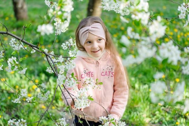 Bello ritratto della bambina vicino ad un ciliegio sbocciante Foto Premium