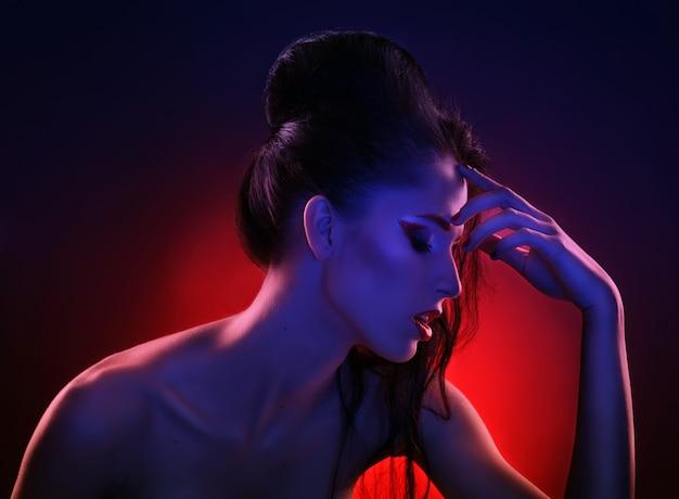 Bello ritratto delle donne alla luce rossa e blu Foto Premium