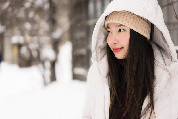 Bello sorridere asiatico della giovane donna felice per il viaggio nella stagione invernale della neve Foto Gratuite