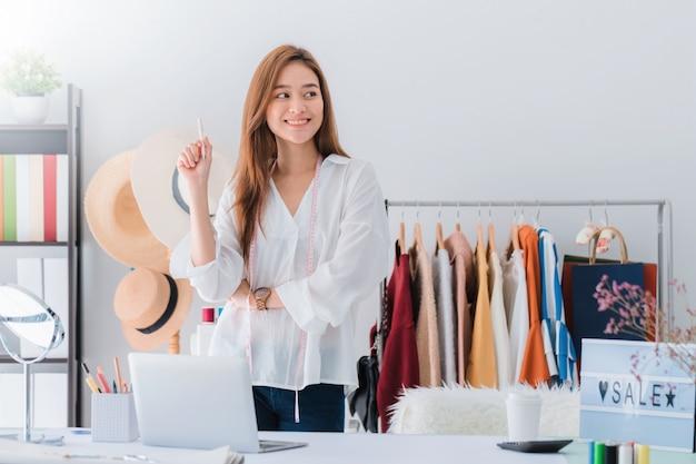 Bello stilista asiatico della donna che sta nel negozio di vestiti Foto Premium
