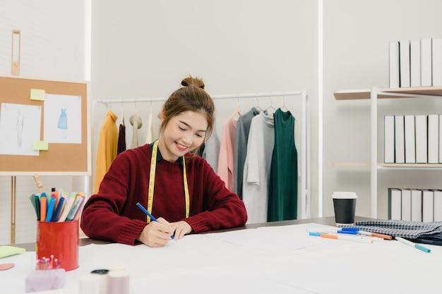 Bello stilista femminile asiatico professionista che lavora con gli schizzi del tessuto Foto Gratuite