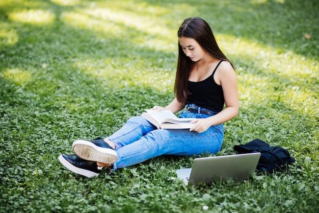Bello studente asiatico che tiene le annotazioni in taccuino di carta mentre studiando online con il computer portatile, sedendosi sull'erba, all'aperto Foto Gratuite