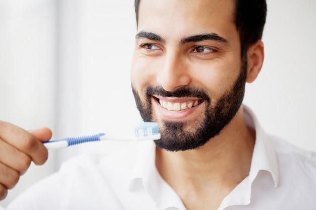 Bello uomo sorridente che pulisce i denti bianchi sani con la spazzola Foto Premium