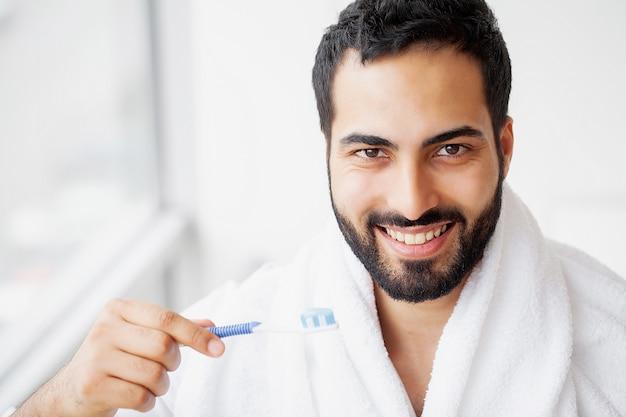 Bello uomo sorridente che pulisce i denti bianchi sani con la spazzola. Foto Premium