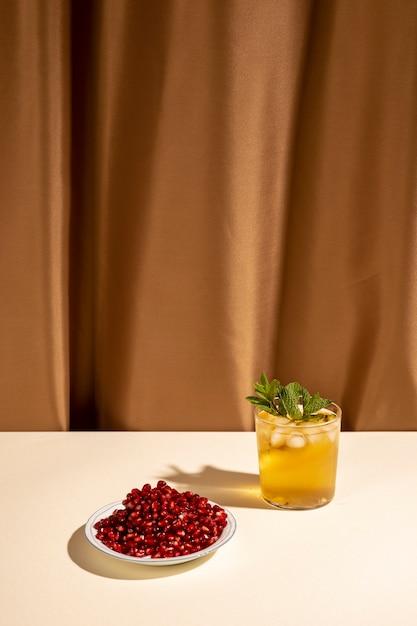 Bere bicchiere di cocktail con semi di melograno sul piatto sul tavolo davanti alla tenda marrone Foto Gratuite