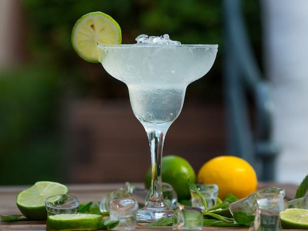 Bere cocktail fresco con alcool, cubetti di ghiaccio e una fetta di lime in un bicchiere Foto Gratuite
