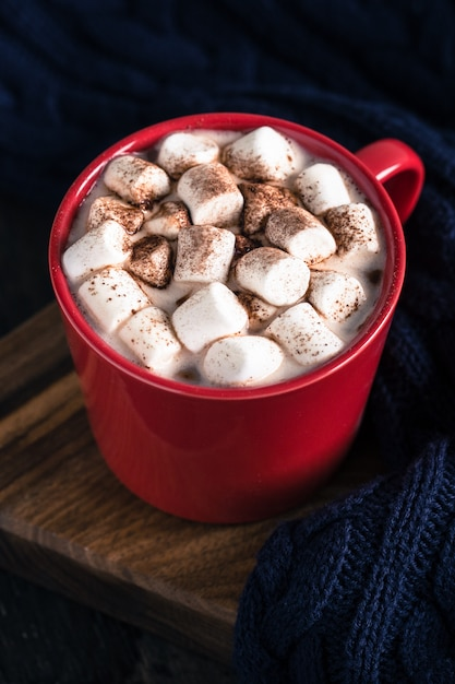 Bevanda calda invernale o autunnale, cioccolata calda o cacao, marshmallow e maglione lavorato a maglia Foto Premium