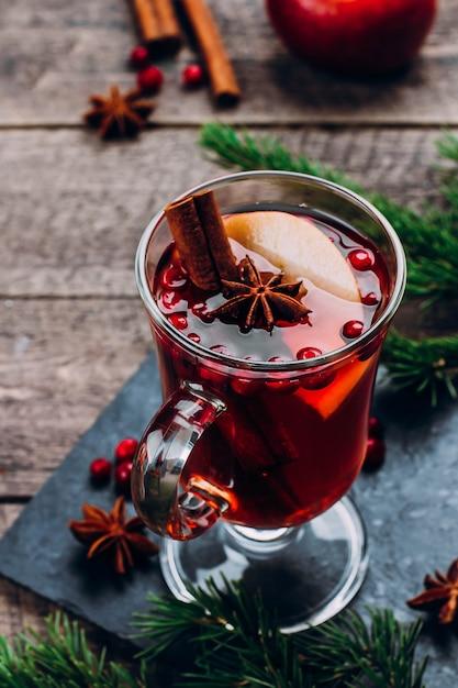 Bevanda calda per le vacanze. vin brulè in vetro con spezie e mela sul tavolo di legno Foto Premium