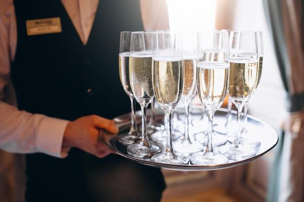 Bevanda del servizio del cameriere su un vassoio in un ristorante Foto Gratuite