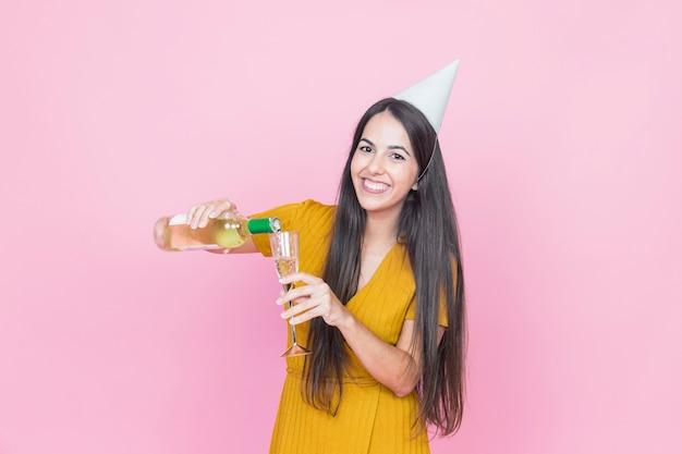 Bevanda di versamento della donna felice in vetro su fondo rosa Foto Gratuite
