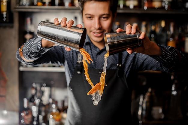 Bevanda di versamento sorridente del giovane barista con le fette di frutta arancio fresca Foto Premium