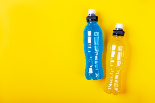 Bevanda energetica isotonica. bottiglia con liquido trasparente blu e giallo, bevanda sportiva Foto Premium