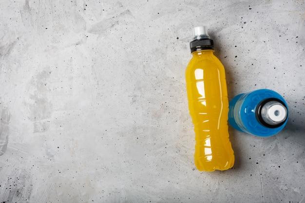 Bevanda energetica isotonica. bottiglie con liquido trasparente blu e giallo Foto Premium