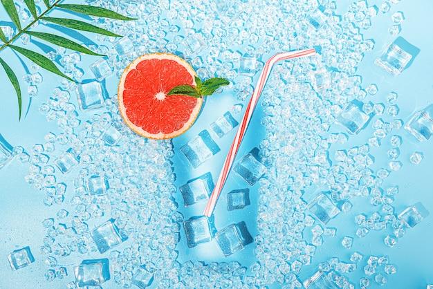 Bevanda fredda. ghiaccio su uno sfondo blu chiaro presentato sotto forma di un bicchiere con un tubulo per un cocktail e una fetta di pompelmo Foto Premium