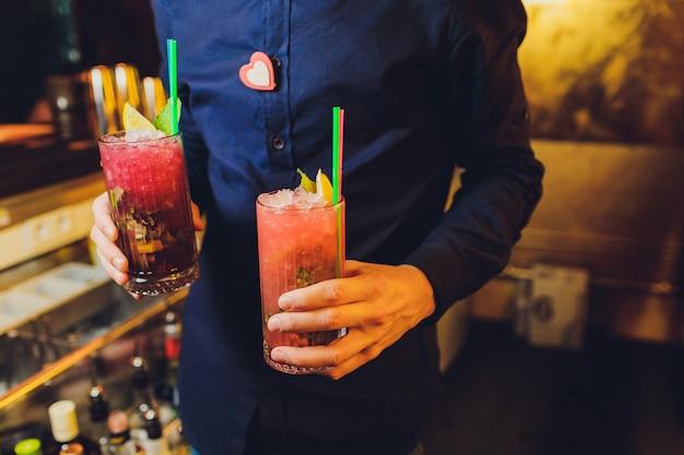Bevanda fresca cocktail nelle mani di un cameriere. Foto Premium