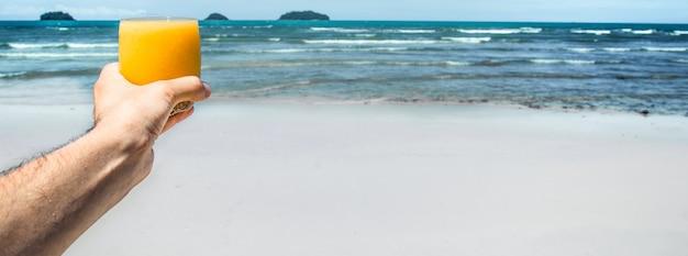 Bevanda fresca in mano dell'uomo sullo sfondo della spiaggia esotica, primo piano Foto Gratuite