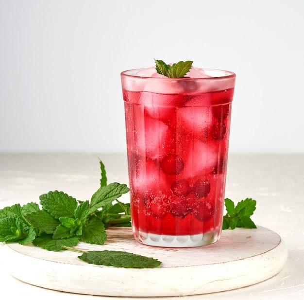 Bevanda rinfrescante estiva con bacche di mirtilli rossi e pezzi di ghiaccio in un bicchiere Foto Premium