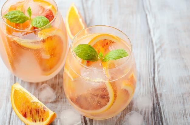 Bevanda rinfrescante fredda con le fette dell'arancia sanguinella in un vetro su una tavola di legno. Foto Premium