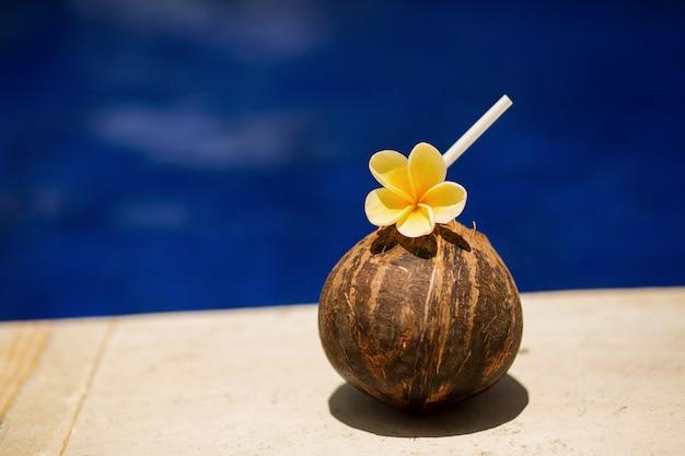 Bevanda tropicale di cocco con fiore giallo, a bordo piscina. hotel rilassante Foto Premium