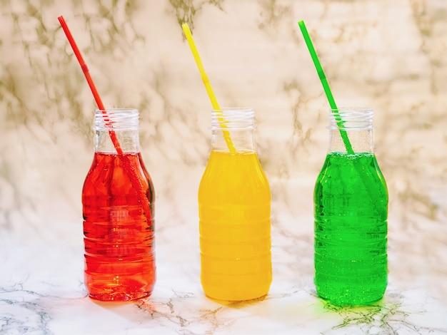 Bevande di limonata colorata naturale in bottiglie di plastica con tubi, bevande isotoniche naturali per il fitness, bevande ambientali organiche Foto Premium