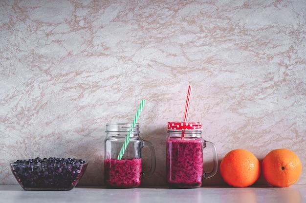 Bevande sane organiche vegetariane della bacca su fondo. pulisci il cibo vegano, mangia bene e bevi il frullato di mirtilli per la dieta Foto Premium
