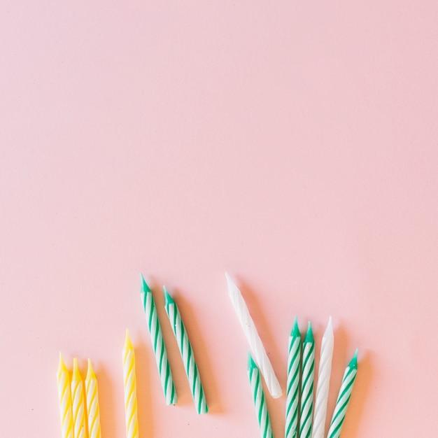 Bianca; le bande verdi e gialle modellano le candele su fondo rosa Foto Gratuite